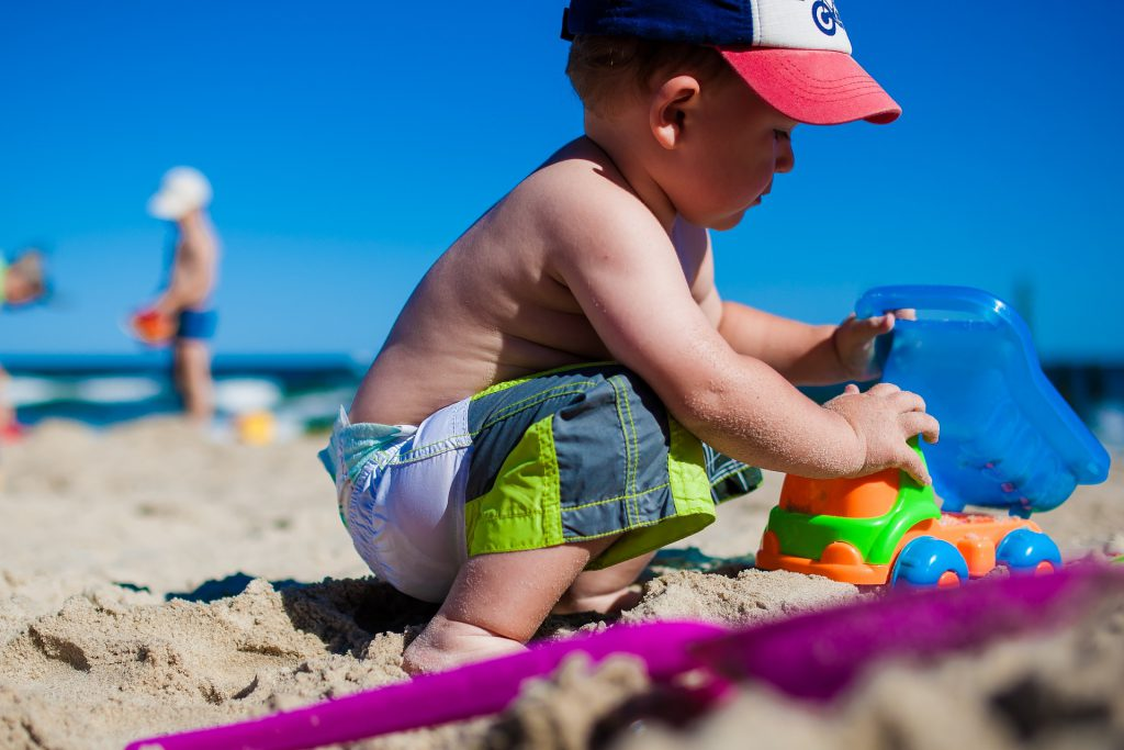 boy playing on sand with beach toys